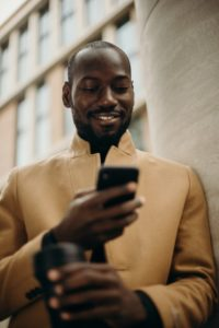 smiling man looking at his phone leaning on concrete pillar 3206079 200x300 - R/E Website Design